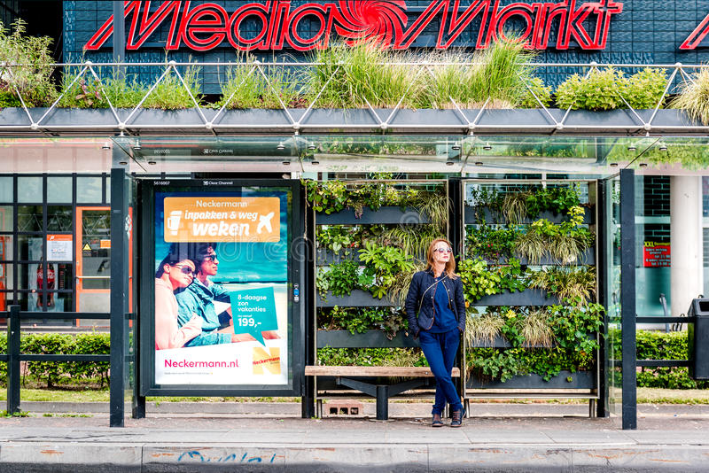 Eindhoven green bus stop. Eindhoven, Netherlands- May 24, 2015: Girl at a Eindhoven green bus stop. The green bus stop was created as part of a competition stock images