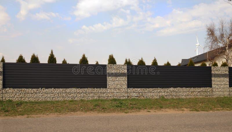 Eindrucksvolles Fechten des Bereichs Eine Wand hergestellt von den gabions und von den Stahlplatten lizenzfreie stockbilder