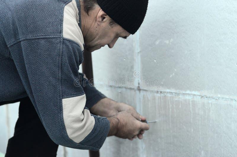Eine ältere Arbeitskraft schafft Löcher in der erweiterten Polystyrenwand für die folgende Bohrung und die Installation eines Reg stockfotografie