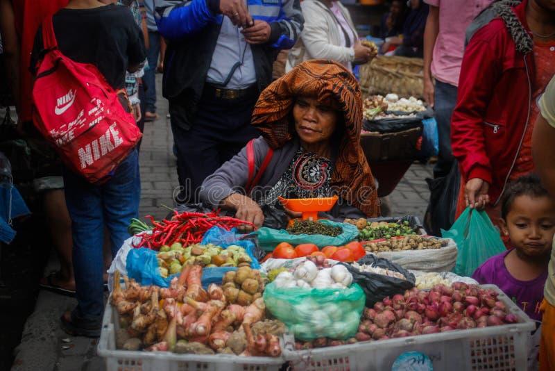 Eine ältere Dame in einem interessanten Hut verkauft Gemüse am lokalen indonesischen authentischen und bunten Straßenmarkt lizenzfreies stockfoto