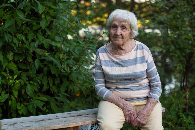 Eine ältere einzige Frau, die auf einer Holzbank im Park sitzt stockfotografie