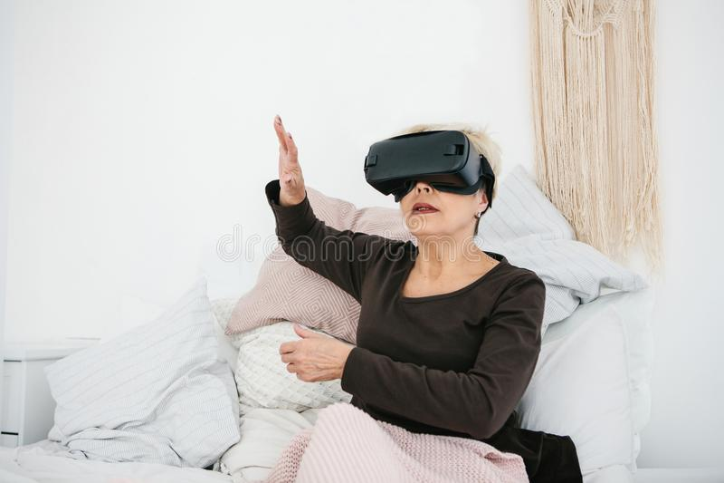 Eine ältere Frau in den Gläsern der virtuellen Realität Eine ältere Person, die moderne Technologie einsetzt lizenzfreies stockfoto