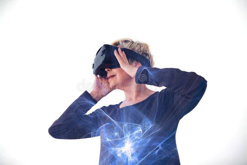 Eine ältere Frau in den Gläsern der virtuellen Realität Eine ältere Person, die moderne Technologie einsetzt lizenzfreies stockbild