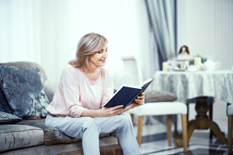 Eine ältere Frau in der Hauptkleidung sitzt auf Sofa With ein Buch in ihren Händen stockfotografie