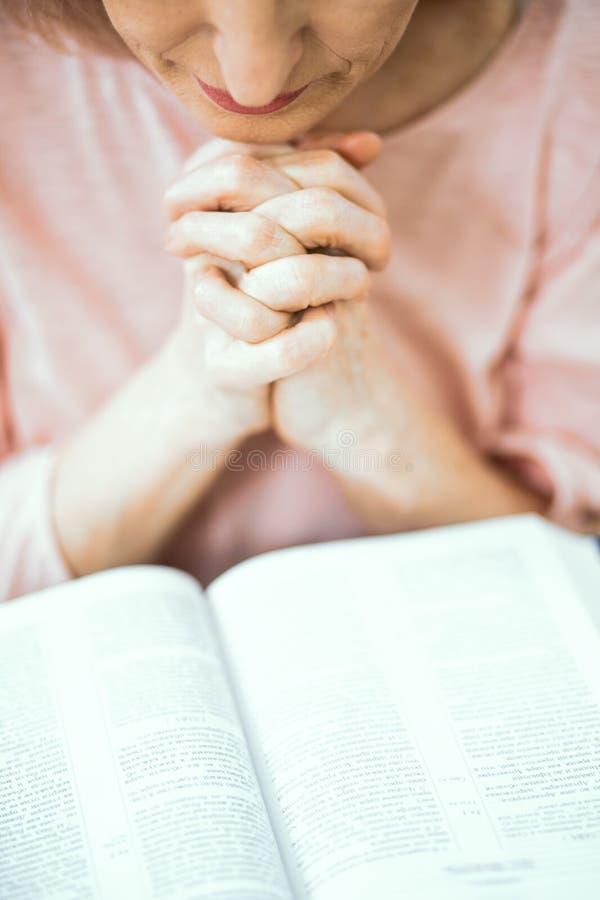 Eine ältere Frau des europäischen Auftrittes betet nahe der Bibel lizenzfreies stockfoto