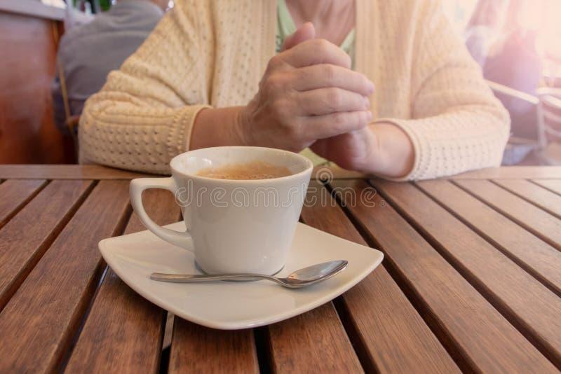 Eine ältere Frau, die durch die Tabelle mit einem Tasse Kaffee in einem Restaurant sitzt stockfotografie