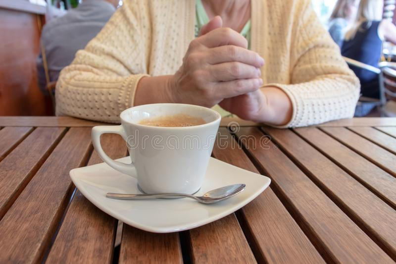 Eine ältere Frau, die durch die Tabelle mit einem Tasse Kaffee in einem Restaurant sitzt stockfoto