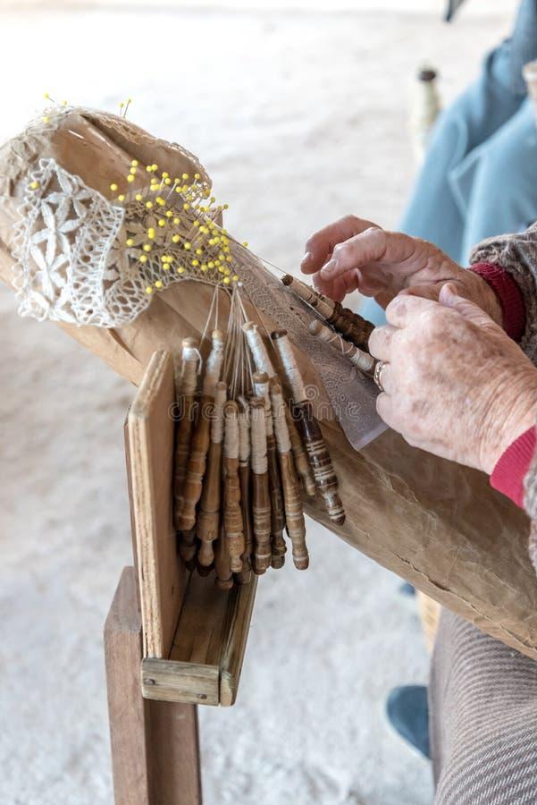 Eine ältere Frau, die an handgemachter Spitze oder bizzilla arbeitet stockbilder