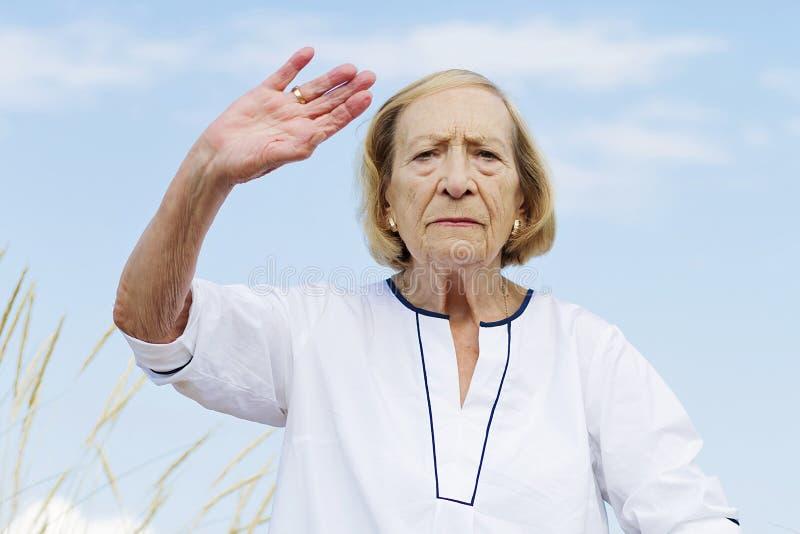 Eine ältere Frau, die Tai Chi übt lizenzfreie stockbilder