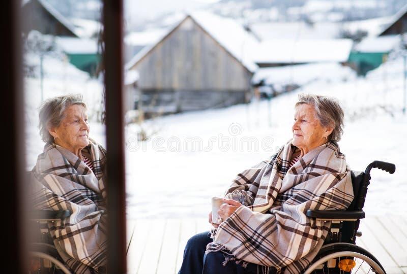 Eine ältere Frau draußen auf einer Terrasse im Winter lizenzfreie stockfotos