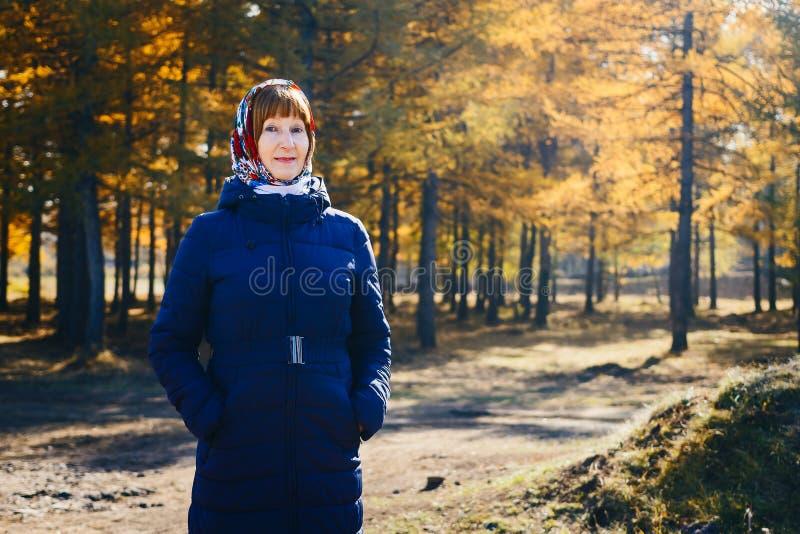 Eine ältere Frau in einem dunklen Mantel im Herbst im Wald lizenzfreie stockfotos
