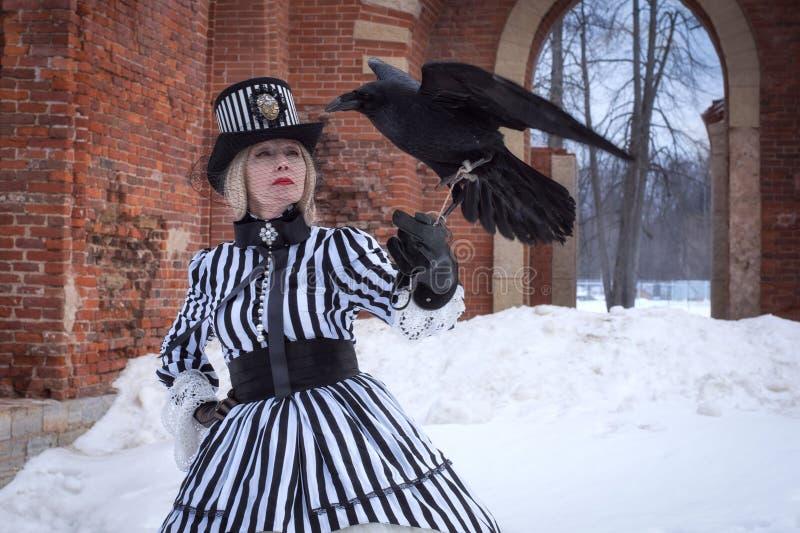 Eine ältere Frau in einem gotischen Kleid mit einem schwarzen Rabenhut auf Natur im Winter stockfotos
