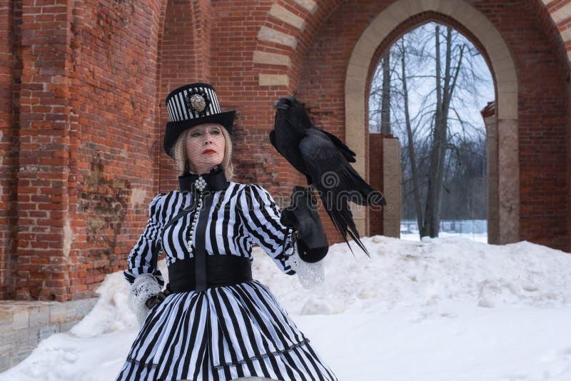 Eine ältere Frau in einem gotischen Kleid mit einem schwarzen Rabenhut auf Natur im Winter lizenzfreie stockfotos