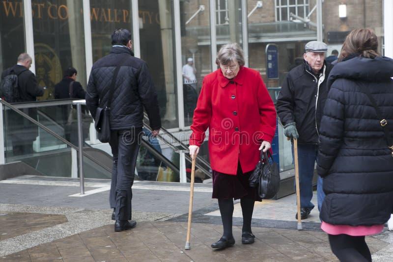 Eine ältere Frau in einem roten Mantel mit einem Stock kam aus den Ausgang an Liverpool-Station heraus lizenzfreies stockfoto