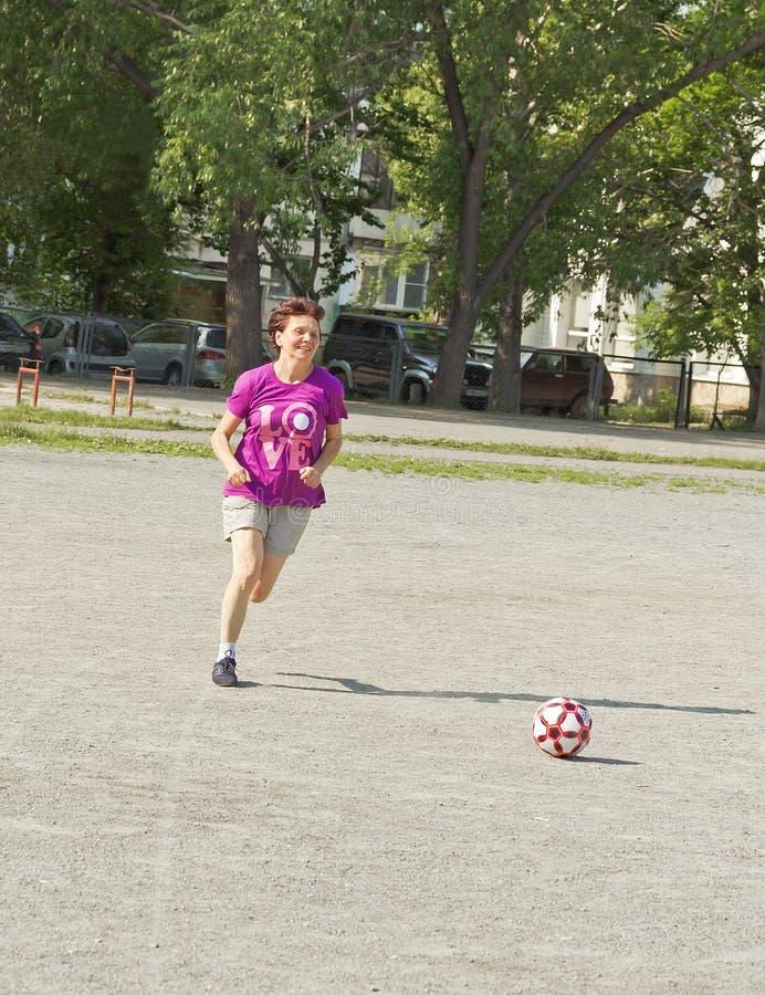 Eine ältere Frau läuft über den Spielplatz mit einem Fußball lizenzfreie stockfotografie