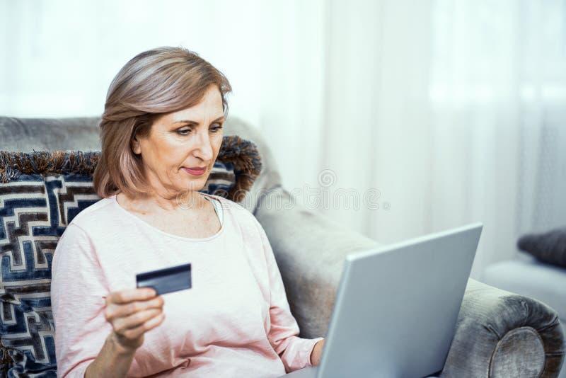 Eine ältere Frau mit einer Kreditkarte in ihrer Hand zahlt für einen on-line-Kauf stockfotos