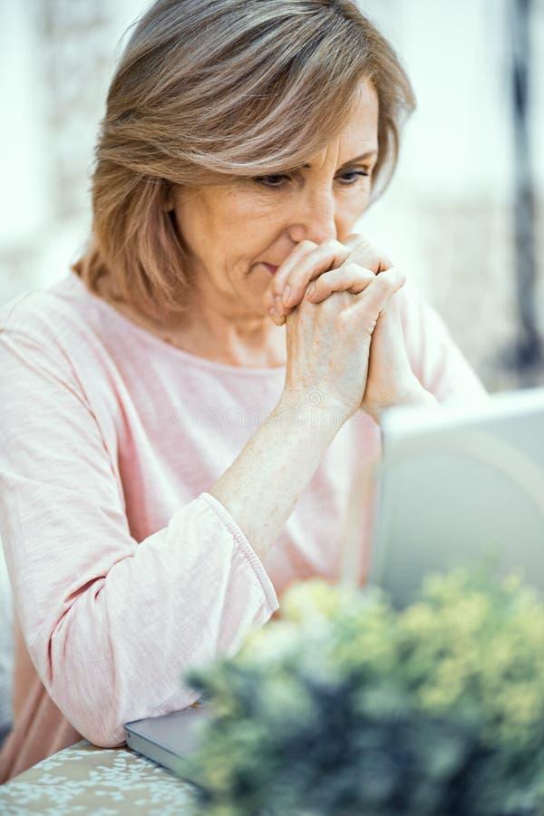 Eine ältere Frau mit ihren Händen, die vor ihr gefaltet werden, betrachtet aufmerksam einem Laptop-Monitor lizenzfreie stockfotos