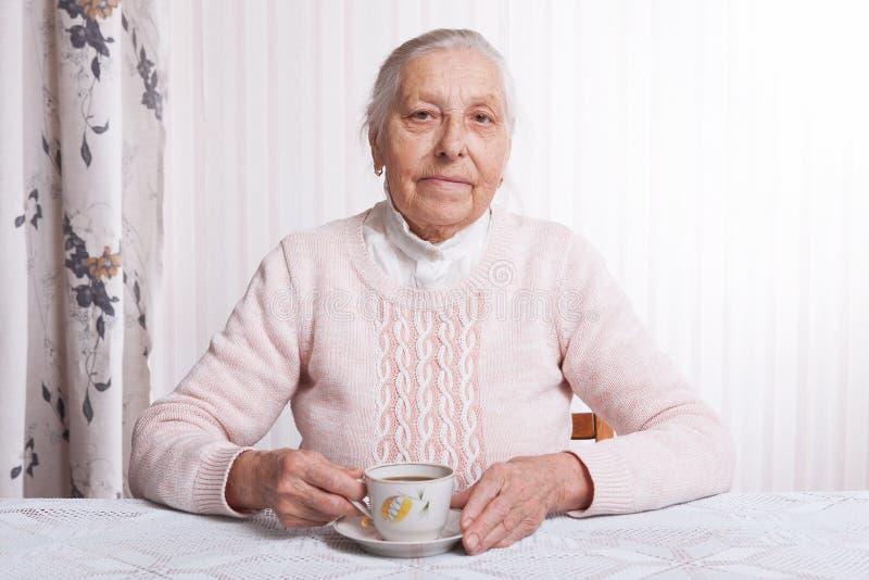 Eine ältere Frau trinkt Tee zu Hause Ältere Frau, die bei Tisch Tasse Tee in ihrer Handnahaufnahme hält stockbild