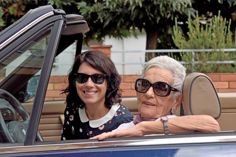 Eine ältere Frau und eine junge Frau, die ein Kabriolett fährt stockbild