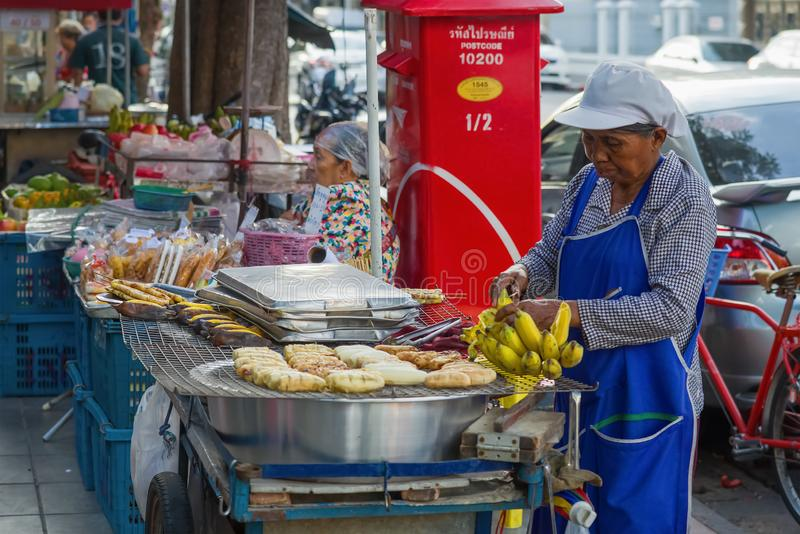 Eine ältere Frau verkauft gebratene bannans Bangkok-Stra?en-Lebensmittel lizenzfreies stockfoto