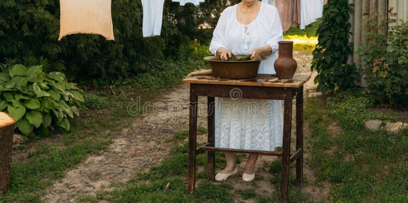 Eine ältere Frau wäscht Kleidung im Garten in der weißen Weinlesekleidung Katze, Kätzchen und Kuh Kleidung trocknet auf einem Sei stockfoto