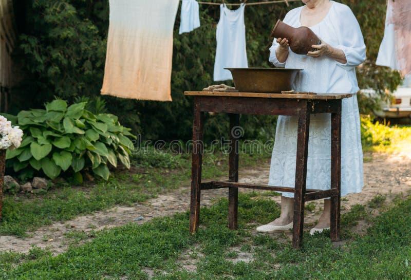 Eine ältere Frau wäscht Kleidung im Garten in der weißen Weinlesekleidung Katze, Kätzchen und Kuh Kleidung trocknet auf einem Sei lizenzfreie stockfotos