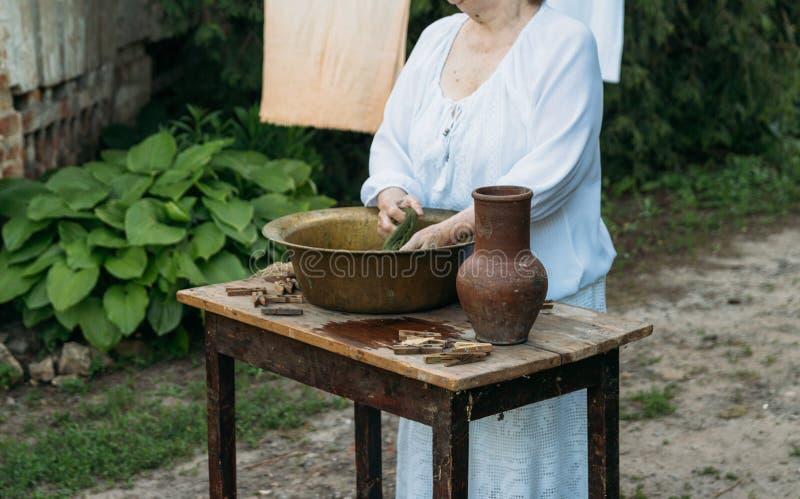 Eine ältere Frau wäscht Kleidung im Garten in der weißen Weinlesekleidung Katze, Kätzchen und Kuh Kleidung trocknet auf einem Sei stockfotos