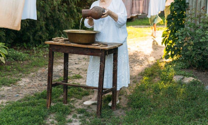 Eine ältere Frau wäscht Kleidung im Garten in der weißen Weinlesekleidung Katze, Kätzchen und Kuh Kleidung trocknet auf einem Sei stockfotografie