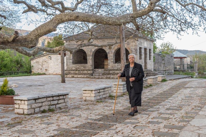 Eine ältere gehende Frau die Straßen von Vitsa in Zagori-Bereich in Nord-Griechenland lizenzfreies stockfoto
