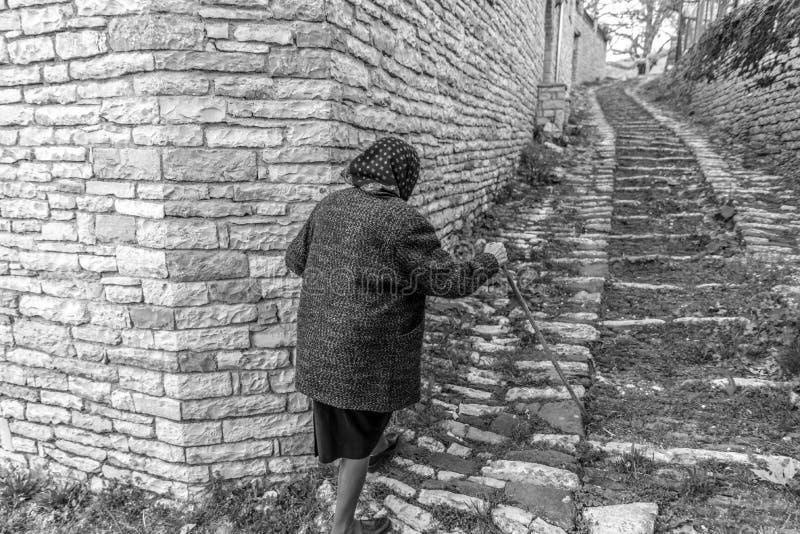Eine ältere gehende Frau die Straßen von Vitsa in Zagori-Bereich in Nord-Griechenland stockfotografie