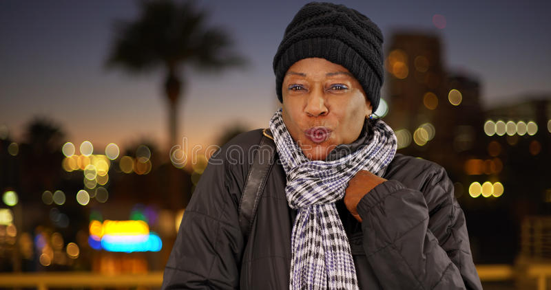Eine ältere schwarze Frau in der warmen Kleidung im Stadtzentrum gelegen nachts lizenzfreie stockfotos