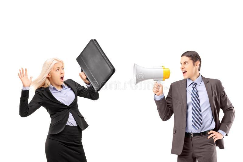 Eine ängstlichgeschäftsfrau und ihr Manager, die mit einem speakerp schreien lizenzfreie stockbilder