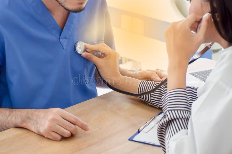 Eine Ärztin benutzt ein Stethoskop auf einem männlichen Patienten stockfoto