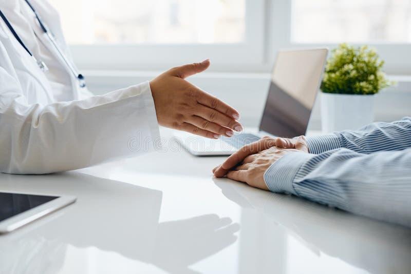 Eine Ärztin bietet eine Handreichung ihrem Patienten an stockfoto