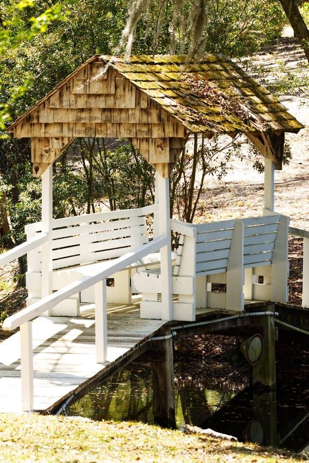 Eine überdachte Brücke in einem Garten mit zwei Sitzbanken stockfotografie