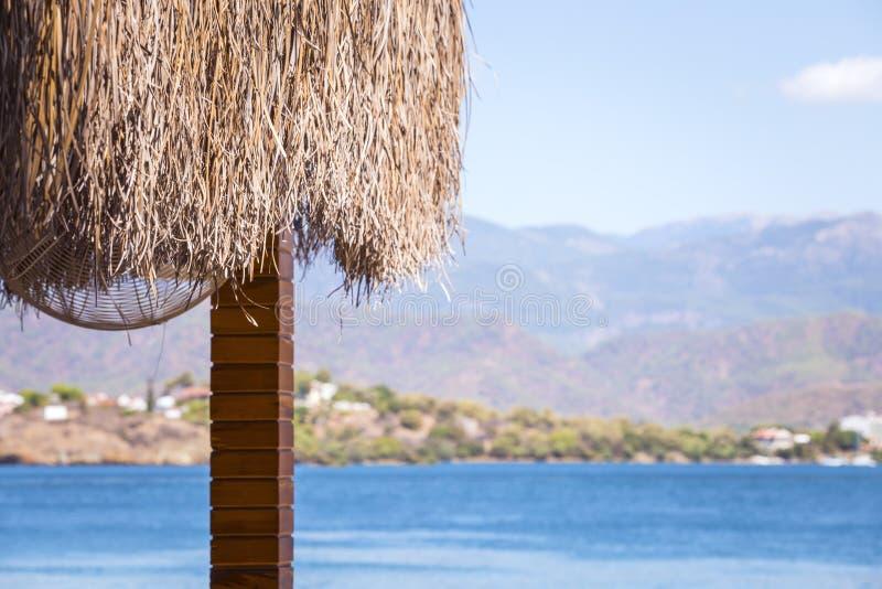 Eine Überdachung von Palmblättern und eine Ansicht über blaues Meer, Berge und Strand stockbilder