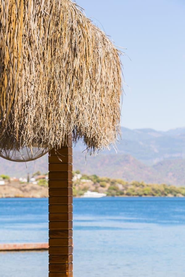 Eine Überdachung von Palmblättern und eine Ansicht über blaues Meer, Berge und Strand stockbild