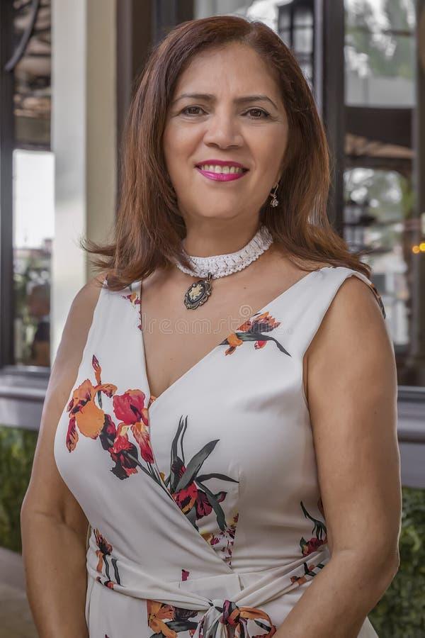 Eine überzeugte hispanische reife Frau wirft für ein OPfoto auf stockbild