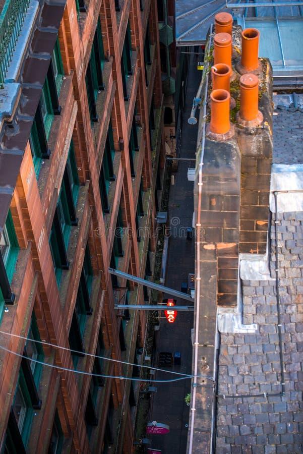 Eine abstrakte Ansicht, die unten auf einem schmalen Durchgang im Glasgow-Stadtzentrum, Schottland, Vereinigtes Königreich schaut stockfoto