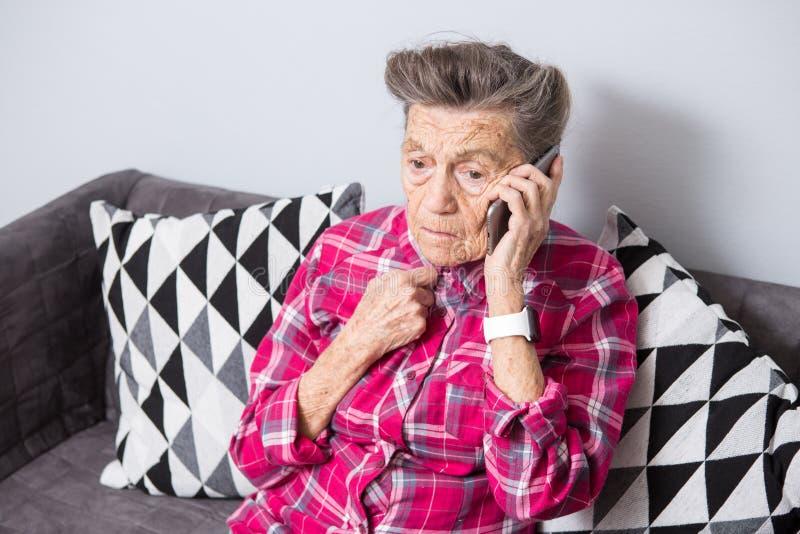Eine alte ältere Frauengroßmutter mit dem grauen Haar sitzt zu Hause auf der Couch unter Verwendung des Handtelefons, ein Telef lizenzfreie stockfotos