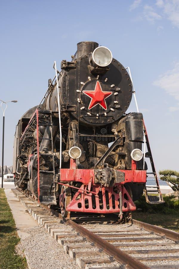 Eine alte Dampflokomotive mit roten Rädern und einem roten Stern steht in einem Freiluftmuseum auf dem Küste Boulevarddamm in Bak stockfoto