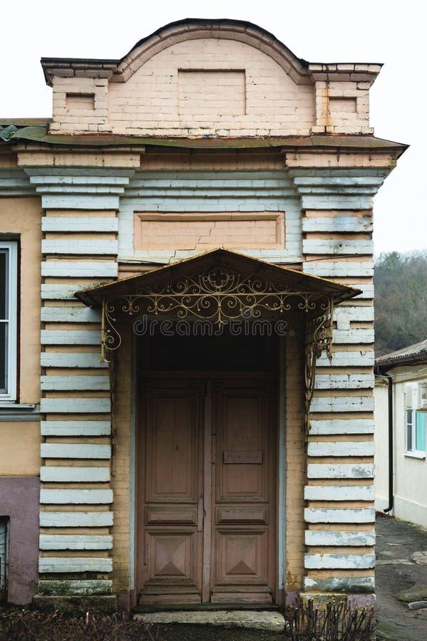 Eine alte europäische Fassade Portal in der Weinleseart mit einem kleinen Dach und einer hölzernen alten Tür stockfotografie