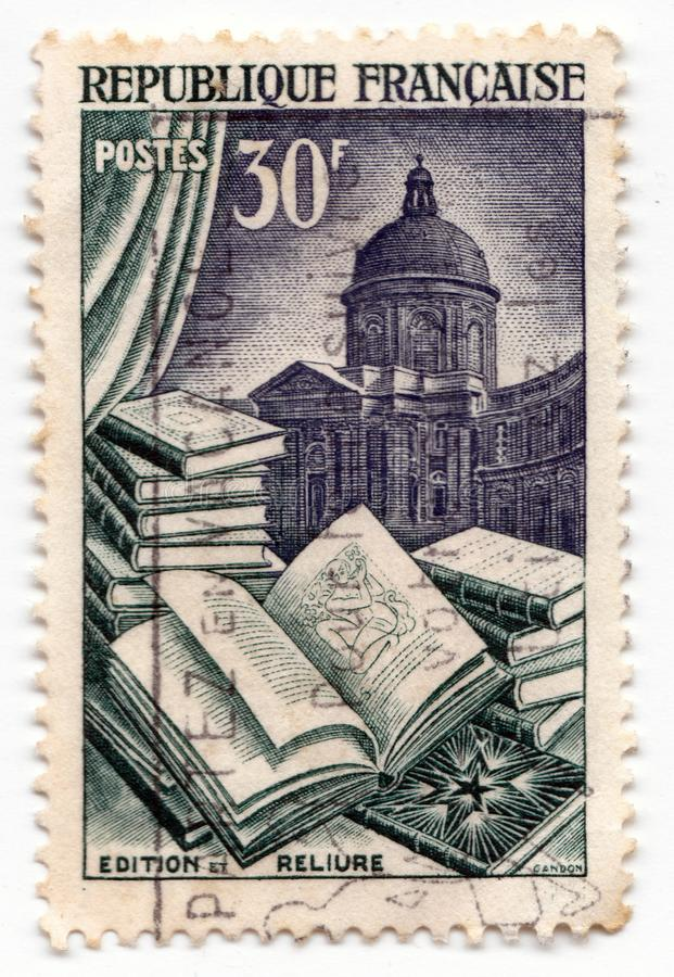 Eine alte französische Briefmarke, die ein offenes Buch mit Illustration und eine Bibliothek im Hintergrund zeigt lizenzfreies stockbild