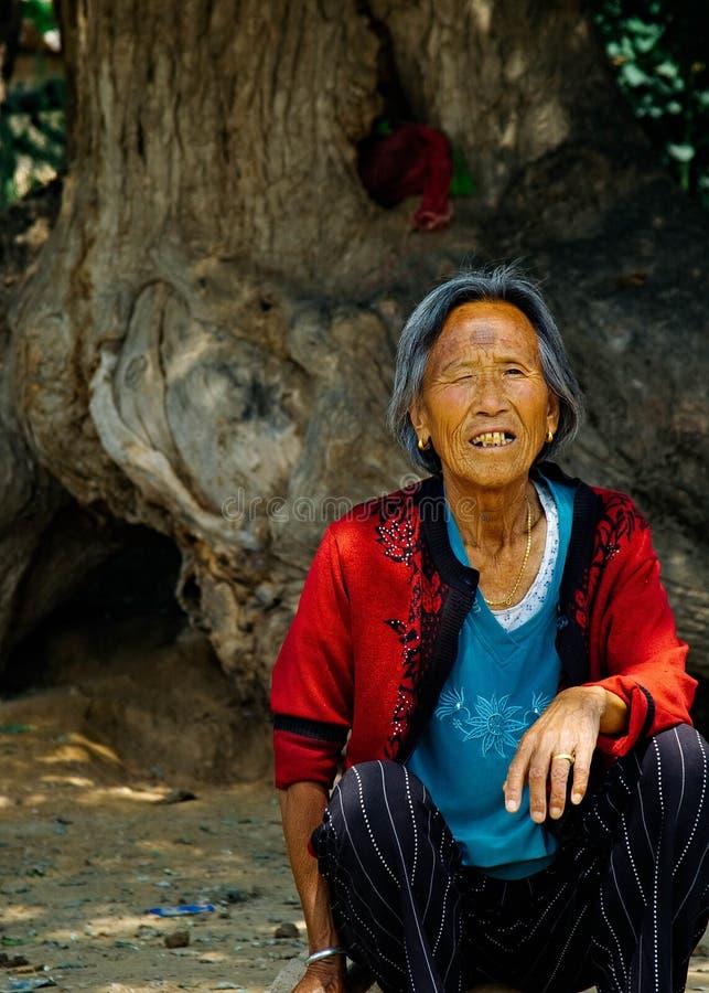 Eine alte Frau, die unter einem alten Baum sitzt stockfoto