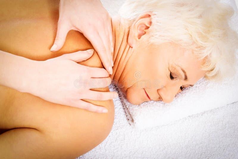 Eine alte Frau hat eine Massage Seifen-, Tuch- und Blumenschneeglöckchen lizenzfreies stockbild