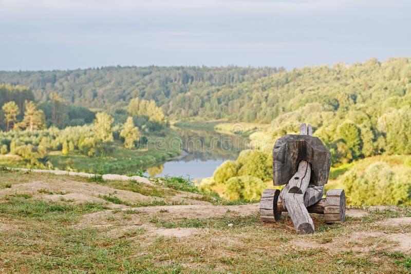 Eine alte hölzerne Kanone als Dekoration steht gegen eine schöne Landschaft mit dem Fluss stockfotos