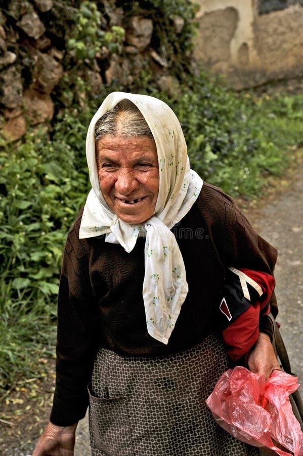 Eine alte mazedonische Dame, die herauf die Straße mit einem Eimer in ihrer Hand geht stockfotos