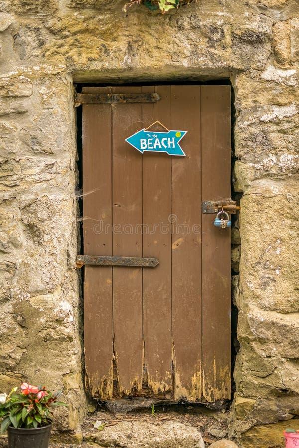 Eine alte schäbige braune Tür mit einem Strandzeichen stockfoto