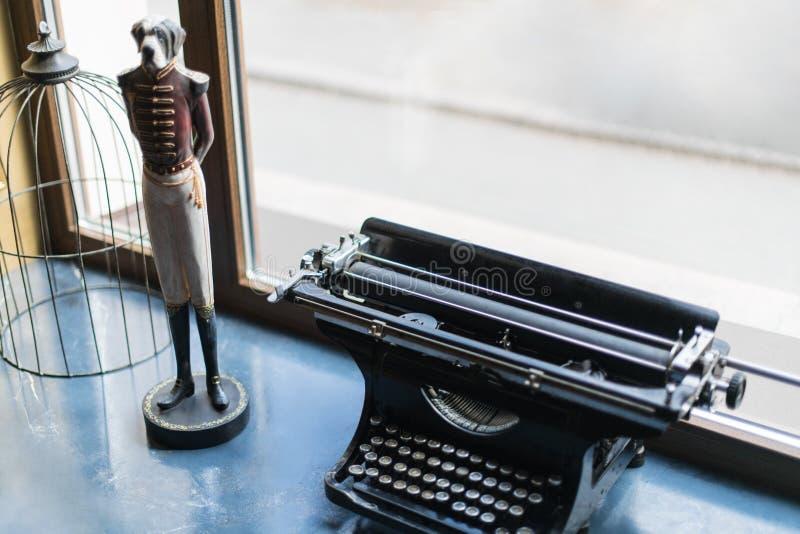 Eine alte Schreibmaschine, eine Zahl eines Hundes und ein Käfig sind auf dem windo lizenzfreies stockfoto