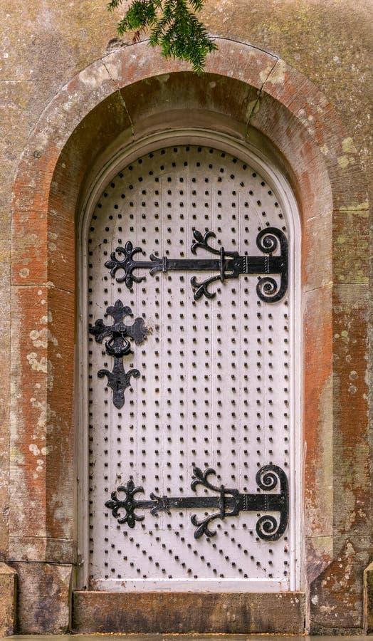 Eine alte weiße Holztür mit ungewöhnlichen Scharnieren und Bolzen lizenzfreie stockfotografie